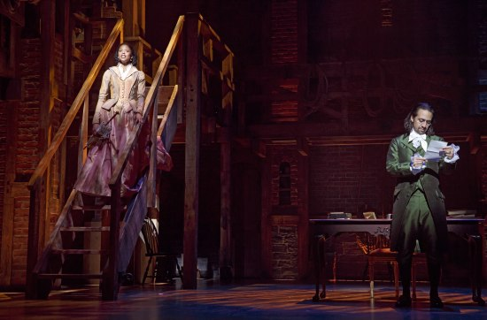 On stage left, Lin-Manuel Miranda as Alexander Hamilton reads a letter, wearing the green suit. On stage right, Renée Elise Goldsberry as Angelica Schuyler Church stands on a stairwell in a pink dress, looking up as though singing.