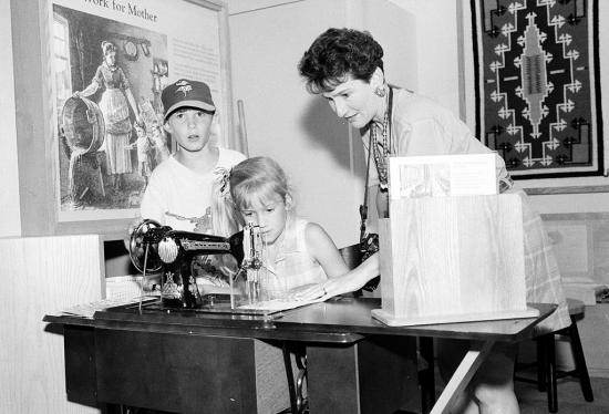 A family gathers around a hands-on sewing machine