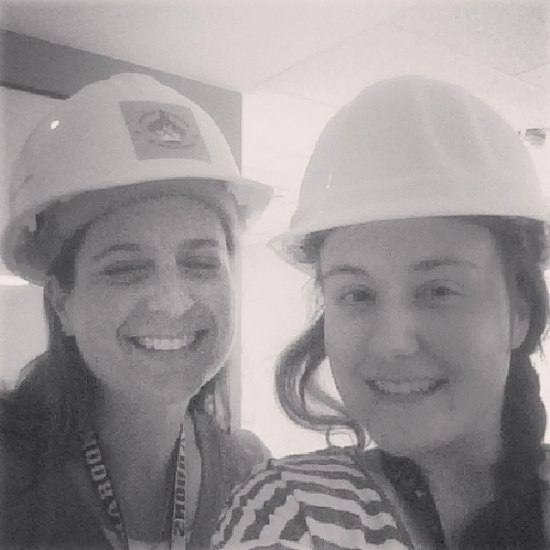 Two women with hard hats smile for a selfie in a black and white photo