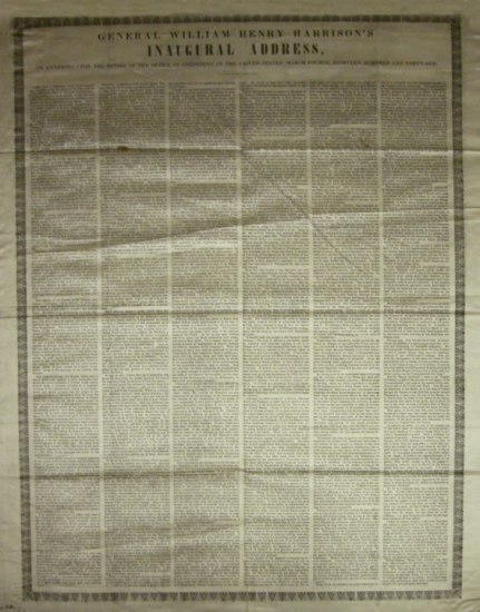A silk scarf in the color of aged paper with a very long speech printed on in tiny letters comprising 6 rows