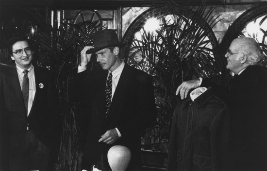 Black and white photo in which three men wearing suits and ties stand in a room with decorative arches. In center, Harrison Ford has a hand on a fedora which is on his head.