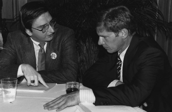 Two men sit at a table speaking.