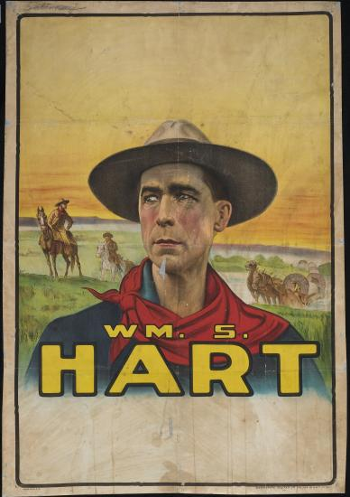 "Hart appears in typical Western costume, with a ten gallon hat and a handkerchief around his neck, against a background showing a line of Conestoga wagons and two horsemen in the American West beneath a yellow sky. ""Wm. S. Hart"" appears beneath the bust image of Hart, who is depicted staring off to his right."