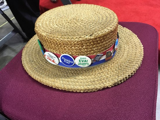 Straw hat with small pins around the brim
