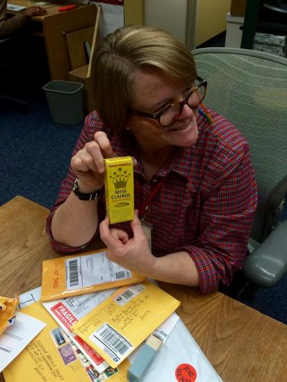 Heather with a pile of mail and a historic box of Miss Clairol, which is yellow