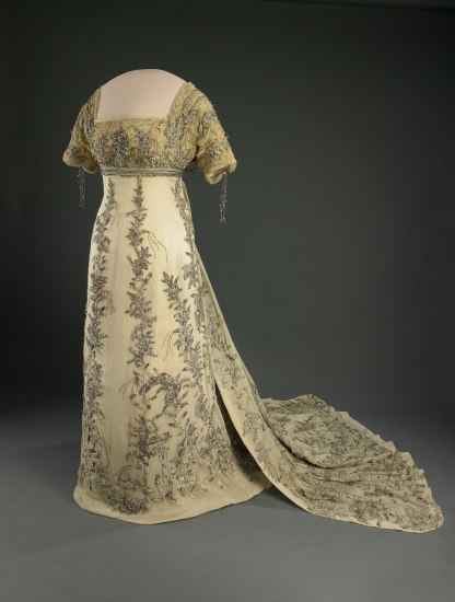 Yellow gown with square neckline and almost elbow-length sleeves. Silver details in silver beads. Short train.