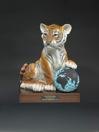 An award on a short wooden base of a young tiger with its paw on what appears to be a golfball painted light blue with the world on it.