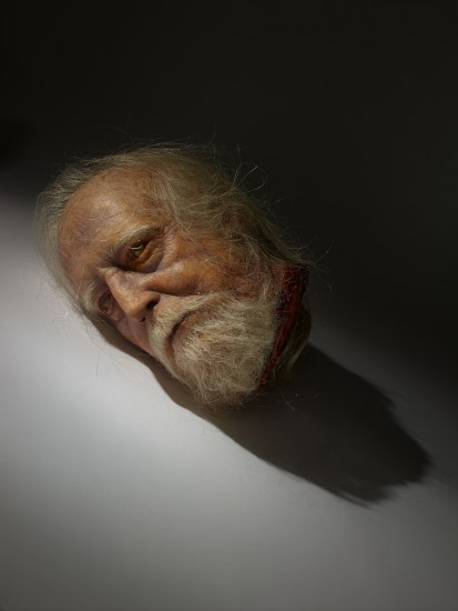 A realistic decapitated head of an elderly man with silver hair and beard. His eyes are open and cloudy with a look of weary resignation.