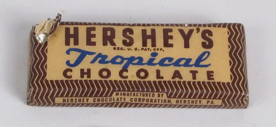"""Brown, yellow, and blue wrapped """"Hershey's Tropical Chocolate"""" bar. Small print on the top reads, """"REG. U.S. PAT. OFF"""". Small print on the side of bar reads, """"MANUFACTURED BY HERSHEY CHOCOLATE CORPORATION, HERSHEY, PA."""" The top left corner of the wrapper is torn, revealing the inner foil wrapping."""