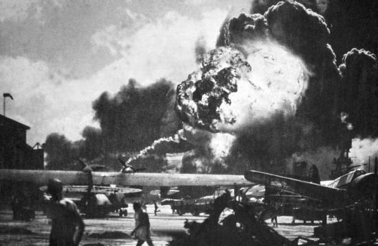 A black and white photo showing plumes of smoke in the background and planes on fire on a flat surface. Men can be seen walking and looking at the explosions.