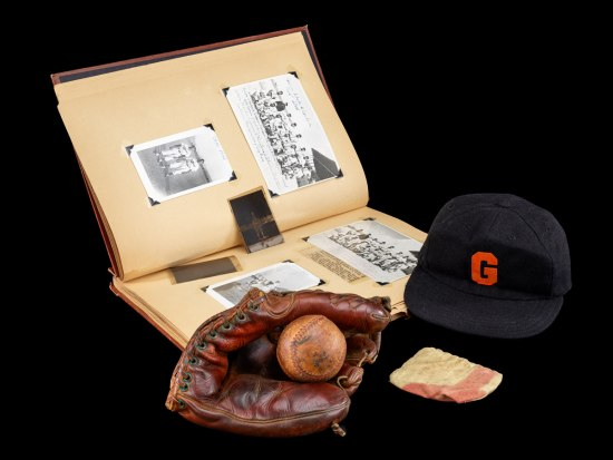 A selection of the objects donated to the museum by Leopoldo Martinez includes a baseball cap, glove, ball, and scrapbook. The scrapbook is opened to showcase the photos that Martinez affixed to various pages.
