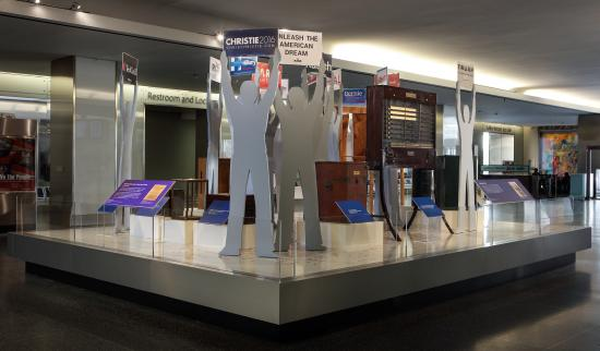 Display in which figures hold up contemporary campaign signs for presidential candidates while standing among historic objects related to voting, such as 1940s voting booths