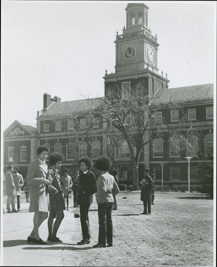 Four students stand in the foreground of this photo depicting a three story building with clocktower in the back and campus grounds. Other students mill around.