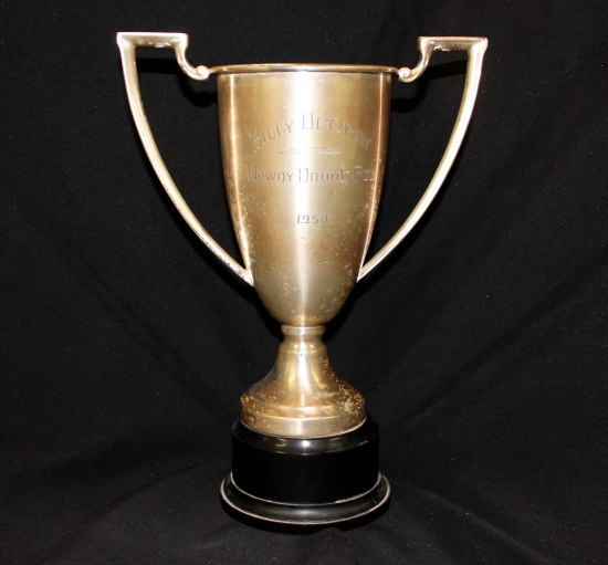 A gold trophy with two handles and words inscribed into it.