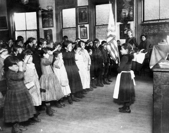 [Black and white photograph of a classroom of elementary-age schoolchildren reciting a pledge to the U.S. flag. Most students are saluting the flag with their hands raised to their brows in a military-style salute. One student stands in the front of the r