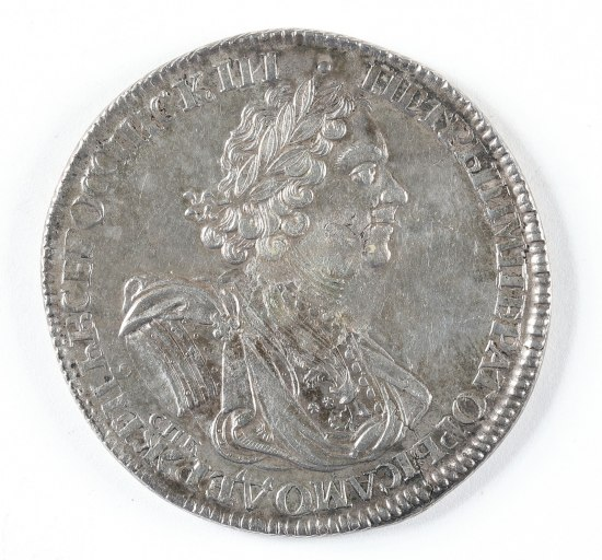 A silver coin with a man's face in profile. He has curly hair, a crown of laurels and classical garb. There is text running around the edges of the coin.