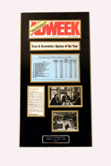 "Photograph of an award board. The board is a tall rectangle with various news articles and photos mounted on it. The board's label reads: ""Sosa & Associates Agency of the Year 1990."""