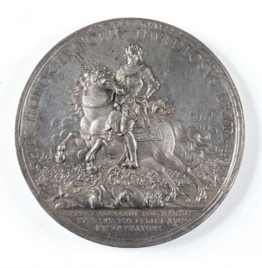 A silver coin depicting a figure on a horse rearing up over what appear to be many fallen bodies