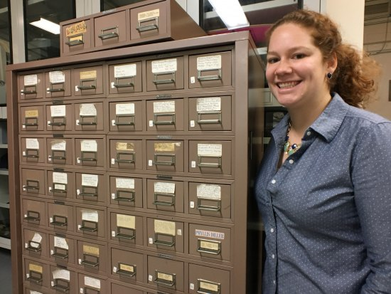 Young woman with curly red hair and a blue button-down shirt smiles, posing beside a filing cabinet, which is beige with white labels and metal handles. The young woman is smiling.