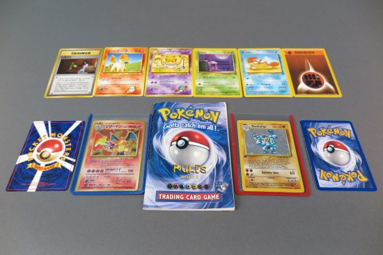 on top of a grey surface, two rows of Pokemon cards are laid out, side by side. There are energy and trainer cards along with cards related to individual Pokemon. Some cards are in Japanese. In the bottom center row is a booklet with instructions for playing the card game.