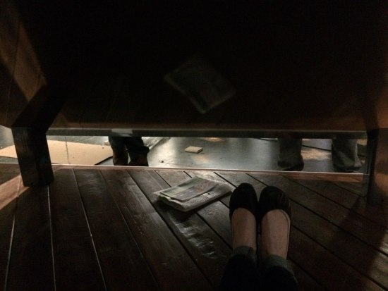A pair of feet wearing womens shoes rests on a wooden platform underneath a sloping sigh of some sort. There is space between whatever is above the wooden platform and one can see several people's legs standing around in a room.