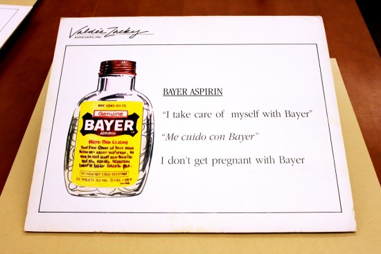 "Photograph of presentation board. The board has a marker-drawing of a Bayer aspirin container, as well as the product's tagline, its direct Spanish translation, and the SPanish translation's back to English. It reads: ""'I take care of myself with Bayer'...'Me cuido con Bayer'...'I don't get pregant with Bayer.'"""