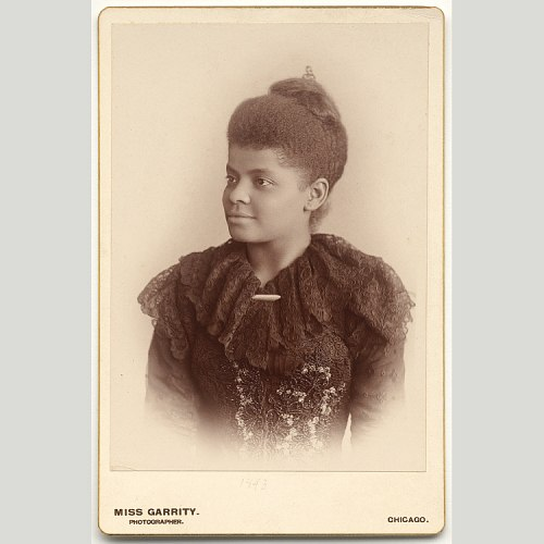 A black and white photograph of Ida B. Wells, a black woman in her 30's, facing towards the left. She is wearing a black dress and her hair is in a bun.