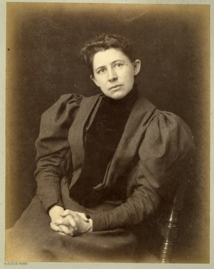 An old photograph of a woman. She wears a dress with voluminous sleeves and sits against a chair, her head tilted and looking away from the camera