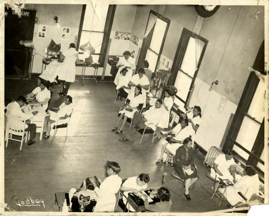 Photograph of women at work in a beauty school. A permanent wave machine can be seen in the corner of the room.