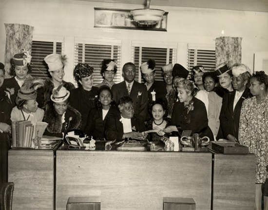 Photograph of official ceremony. Mary McLeod Bethune, seated at desk, accepts a check from Marjorie Stewart Joyner. Both are surrounded by men and women dressed in formal attire.