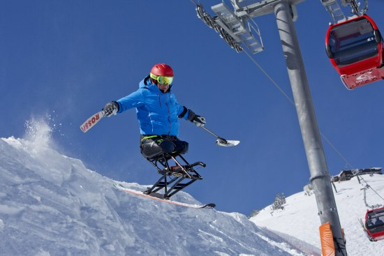 A photo of someone on an adaptive snowboard flying through the air, the sky blue behind them