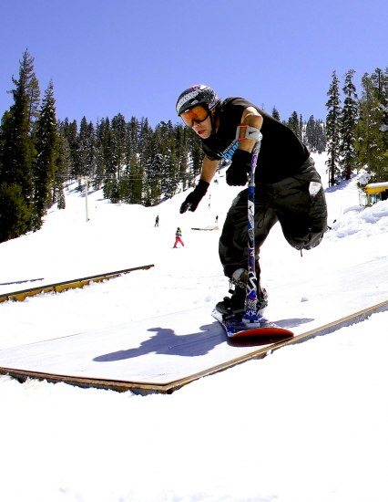 A man stands on a snowboard with a pole that is attached to his left hand. He is outside and there is snow and trees.