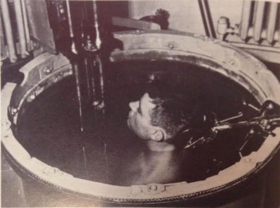 A man is submerged up to his neck in a metal bath that seems to be of some height. Metal rods protrude into the water and he rests his head against some sort of metal headrest.