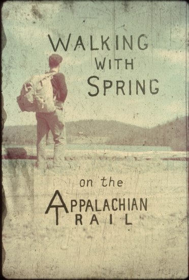 "The cover of a book called ""Walking with Spring on the Appalachian Trail"" The cover is faded and depicts a man from the back who is wearing a backpack and looking out over some wilderness."