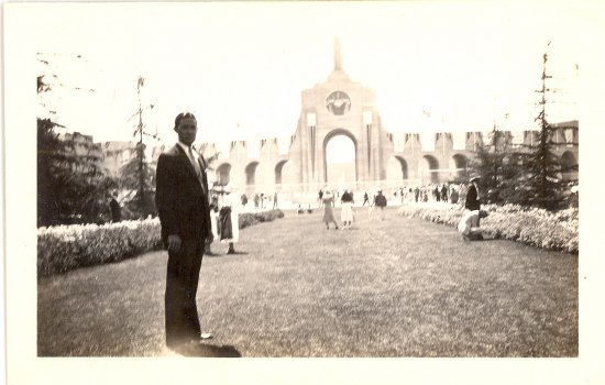 A man stands in the foreground of a black and white photograph. Behind him is an arched opening that people are walking in and out of. The man stands on manicured grass and either side of the lane has bushes and trees.