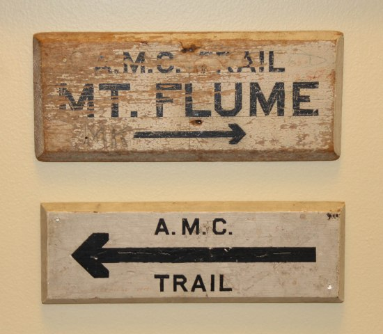 "Two old wooden signs. Neither are very large. They are painted light colors, though it is worn off. One sign says ""A.M.C. Trail Mt. Flume"" and ""A.M.C. Trail"" and both have arrows painted on the bottom."