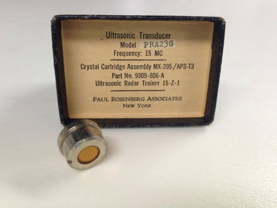 "A box labeled as a ""cartridge"" on the front for an ultrasonic transducer. There is other identifying text on the tan surface with a black border, as well as a metal cup-like object sitting in front with a hole and an opaque amber bottom"