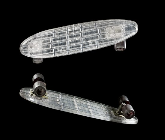 Two views of a skateboard, one from the top and one showing the underneath. The skateboard is made of plastic or some other clear material.