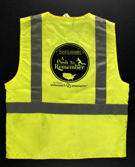 A neon yellow safety vest with reflective stripes. On the back, there is a circle with text regarding the event and the organization, both related to Alzheimer's