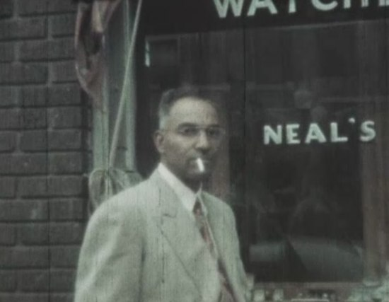 Film still. Gentleman in a suit smoking a cigarette outside store. He is wearing glasses.