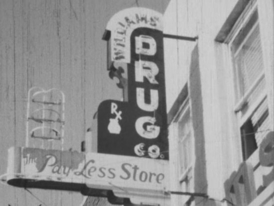 Black and white still from a film. It shows a drug store sign for William's Drug co. Pay-Less Store.