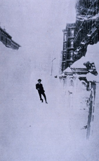 Black and white photo of man wearing a hat leaning against a giant bank of snow. To the right, snow-covered gate or fence and three story building.