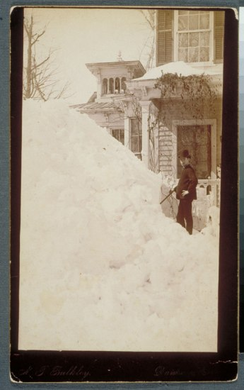 Photograph: Large pile of snow. In right side of photo, a man wearing a hat and holding a cane stands among the snow, which is taller than he is. Behind him, a house with ivy growing on it.