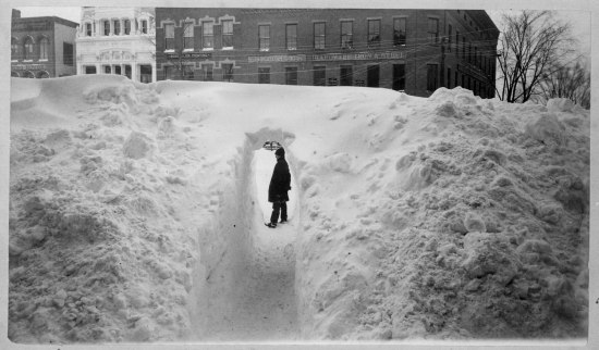 "Black and white photo of a large bank of snow. In the center, a tunnel has been made. A man stands inside the tunnel. Behind him, five buildings over one story high. ""Hardware Iron & Steel"" says the sign on one."