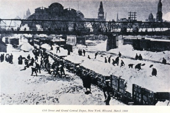 Black and white photo of a train wreck. Dozens of people around the cars, shoveling snow.