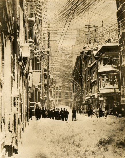 Black and white photo of a group of people standing in a city street that is covered in snow. Many electrical wires overhead. Narrow street, tall buildings. Snow on all surfaces.