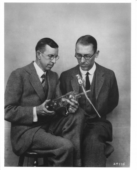 A photograph of two bespectacled men looking at a glass instrument that one of them is holding. The body of the object is like a glass bottle with some sort of metal components inside.