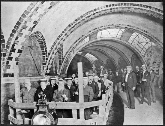 A group of men in hats and suits, stands on the platform and sits in plywood railroad cars beneath the tiled arches of City Hall station.
