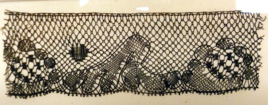 A pattern for lace layed out in black dots on yellowed paper.