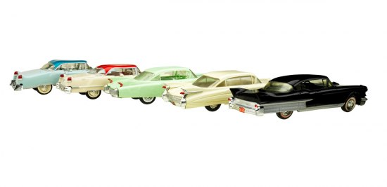 A photograph of five Cadillac models representing model years from 1955 to 1959. The models are posed facing away from the viewer to highlight the rear fenders and tail fins.